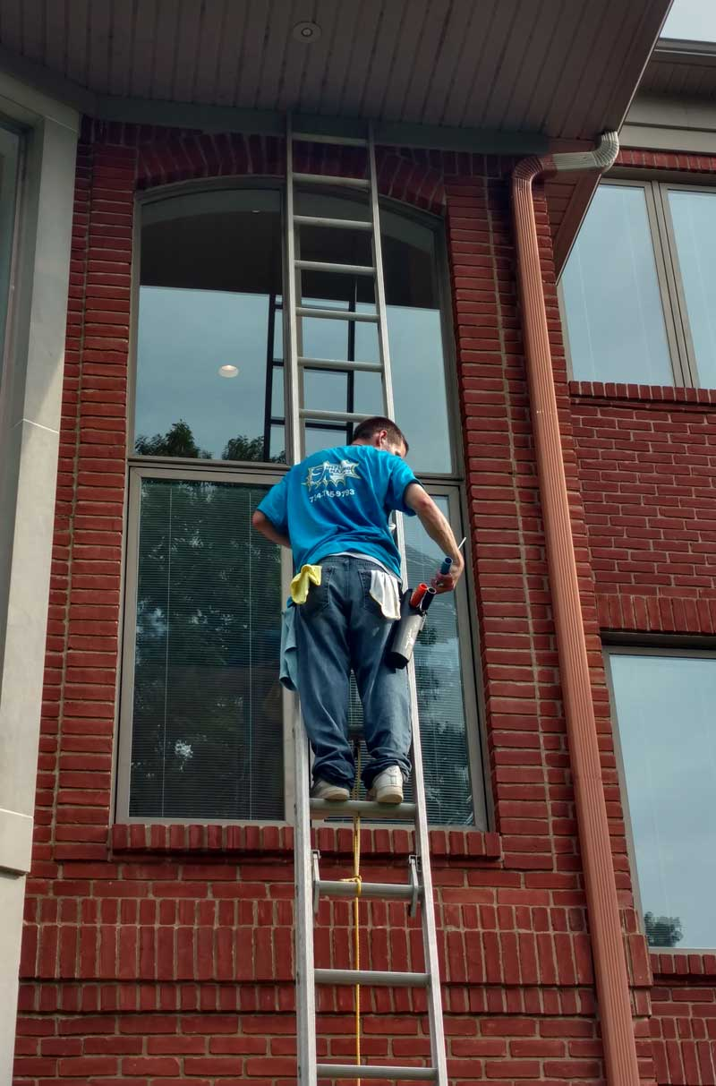 man on ladder cleaning windows